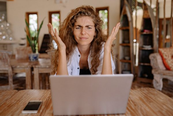 Blond female business owner holds hands up in frustration while looking at her laptop